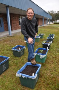"Rex Stanford with ""grow boxes"" made from former recycling containers."